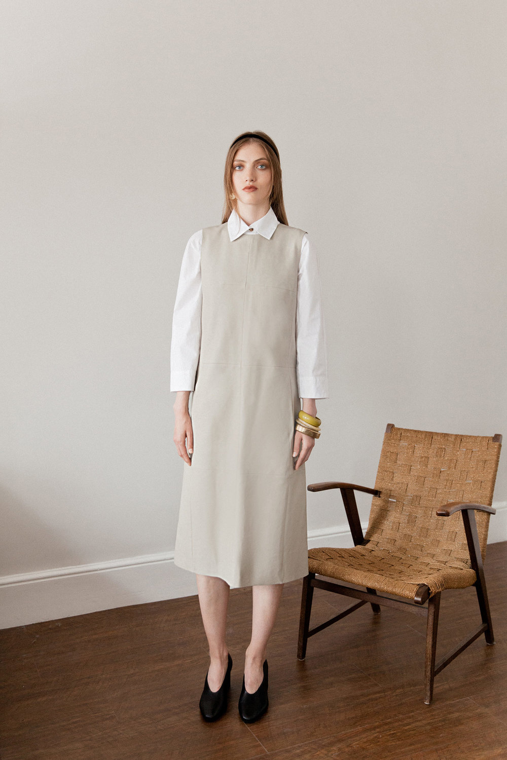 Sculptured leather dress in mineral grey, £290, COS; Jan Machenhauer white shirt, £149, Found; Black leather block heel shoes, £55, M&S; No.25 earrings, £35, Alice Bosc; Brass, Bakelite and Lucite bangles, from a selection, Heavens Bazaar