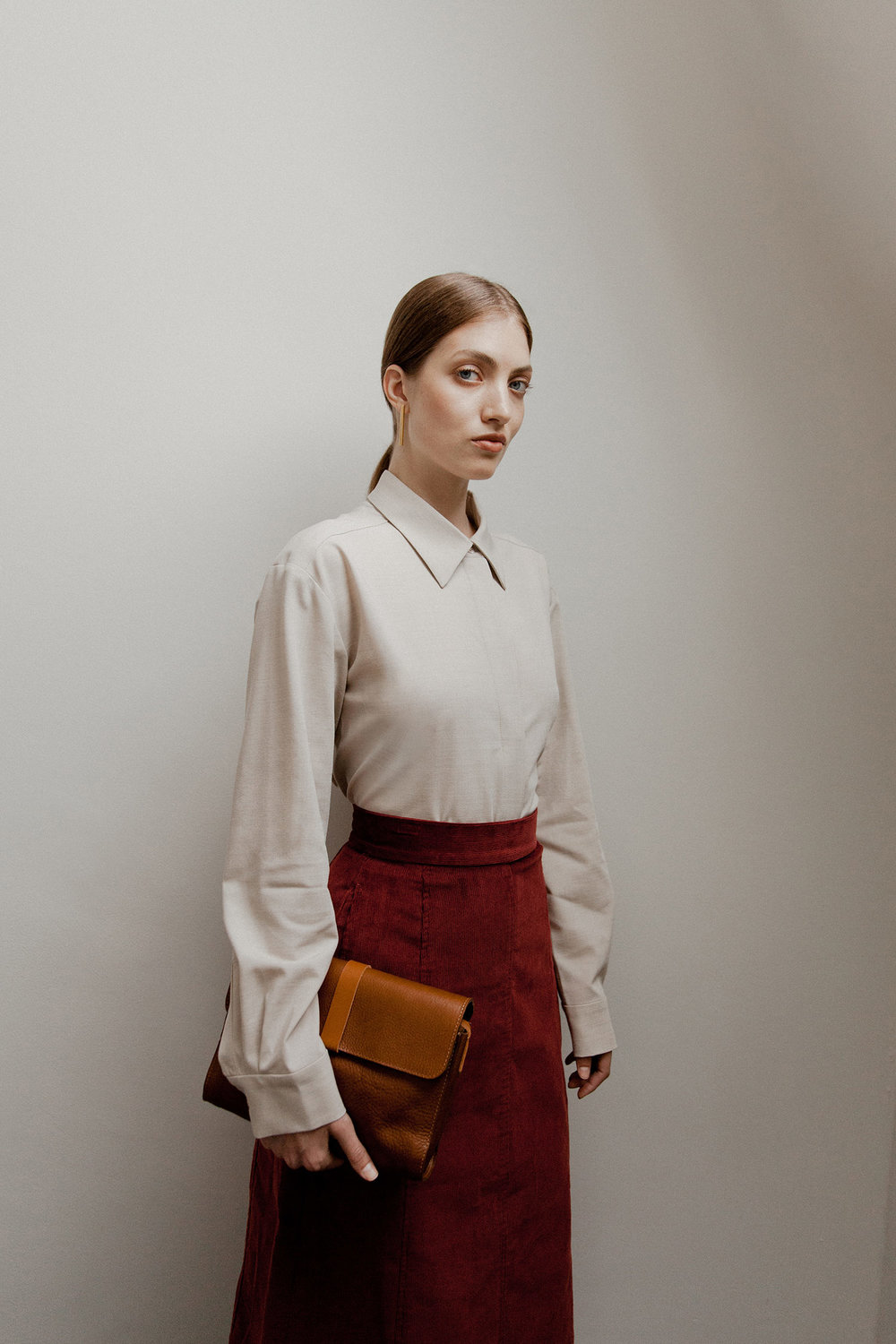 Refabricated shirt in oatmeal, £79, COS; Cord skirt in Boysenberry, £130, Toast; Rhizo leather bag in tan, £230, M.Hulot; Brass bar earrings by Laura Lombardi, £67, Found