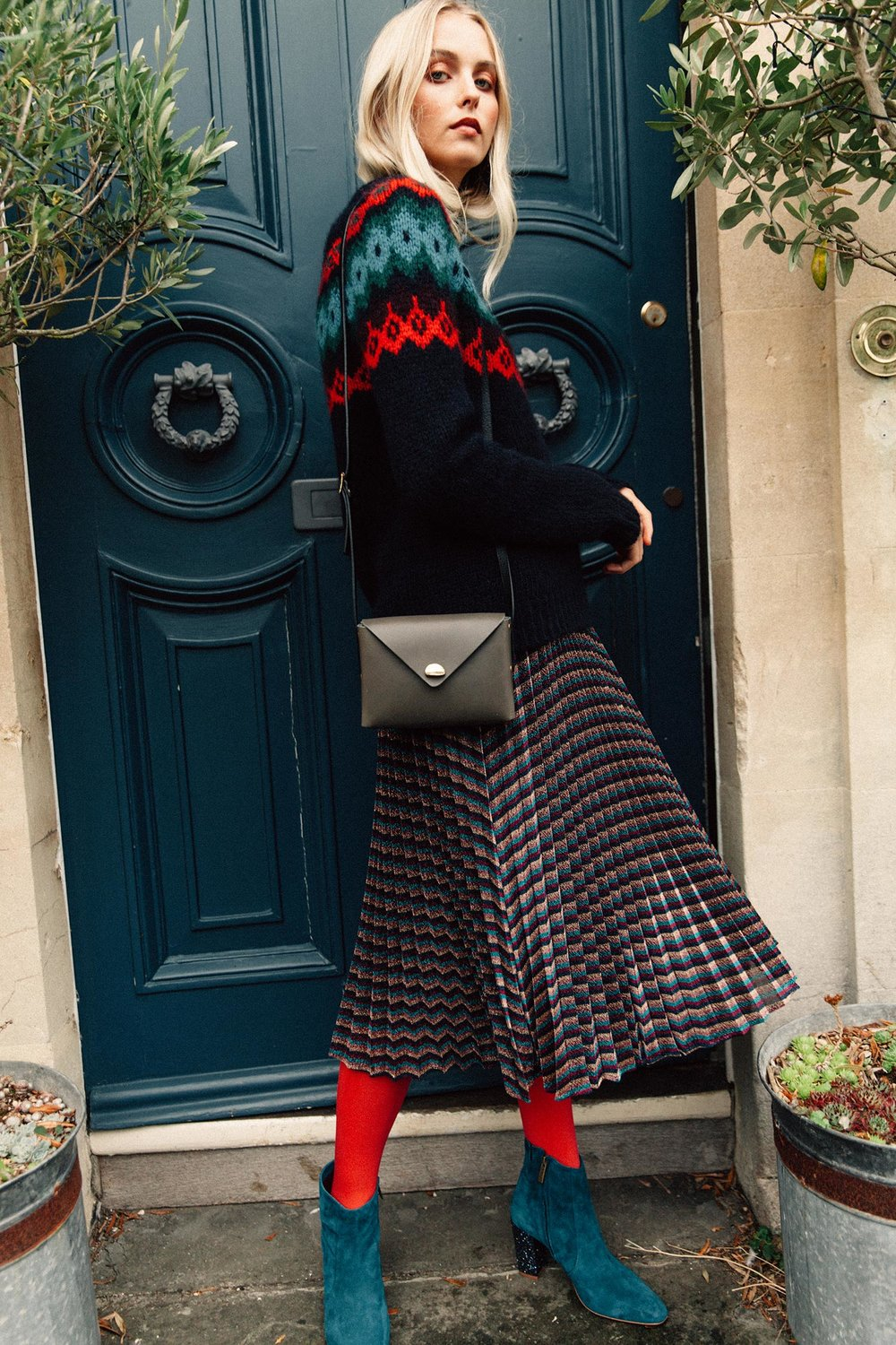 Fair Isle alpaca sweater in navy/multi, £165,  Toast ; Metallic stripe pleated skirt, £159,  Whistles ; Sarsgrove teal suede and glitter ankle boot, £180,   DuoBoots ; Box bag in smoke, £255,  Lucie Cast  at East of Home; 60 denier red opaque tights, £5, Pretty Polly