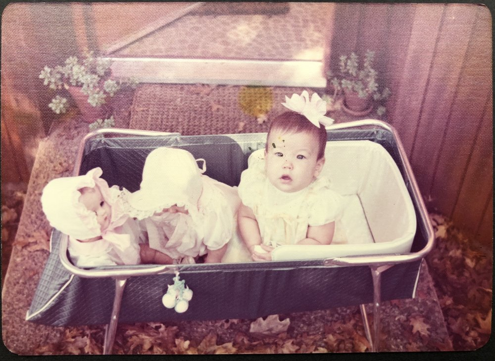 Here I am blue-eyed and eight months old, dressed like a doll in a bassinet on the front stoop. I'm holding my white bootie pried from my foot.