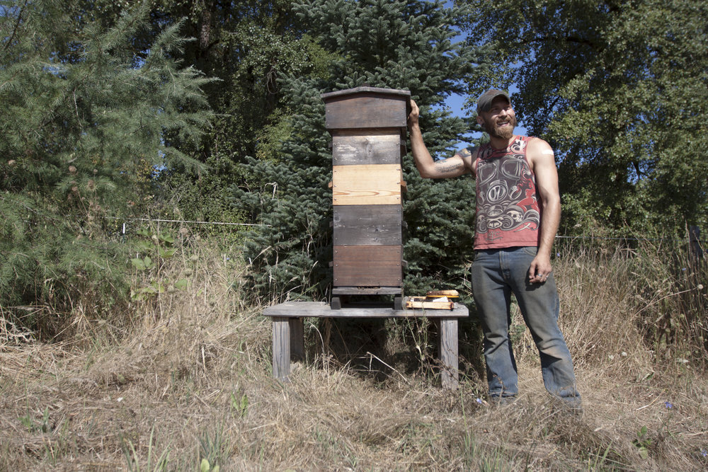 Rogue Farm Corps intern Mike next to honey bee hive.