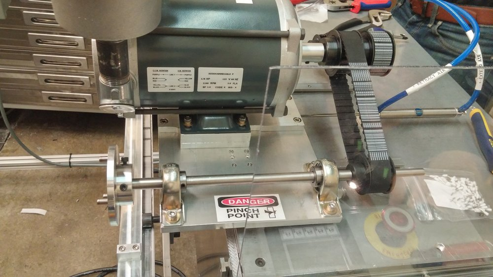 (Above) Driven by a belt drive, three pronged keys on the shafts to engage with rollers. The drive sits on linear rails with a linear actuator to engage with the rollers  (Left) Adhesive spray gun attached to adhesive delivery and pneumatic actuator lines