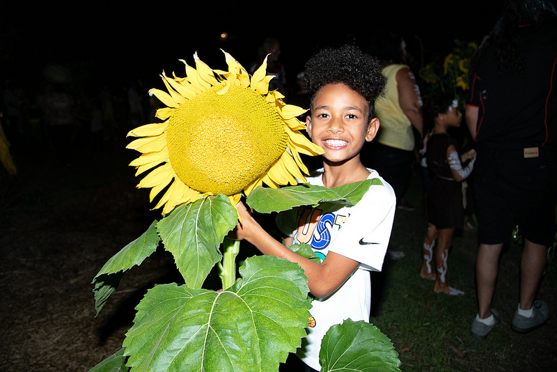 Kids distribute the sunflowers to the crowd at The Beacon