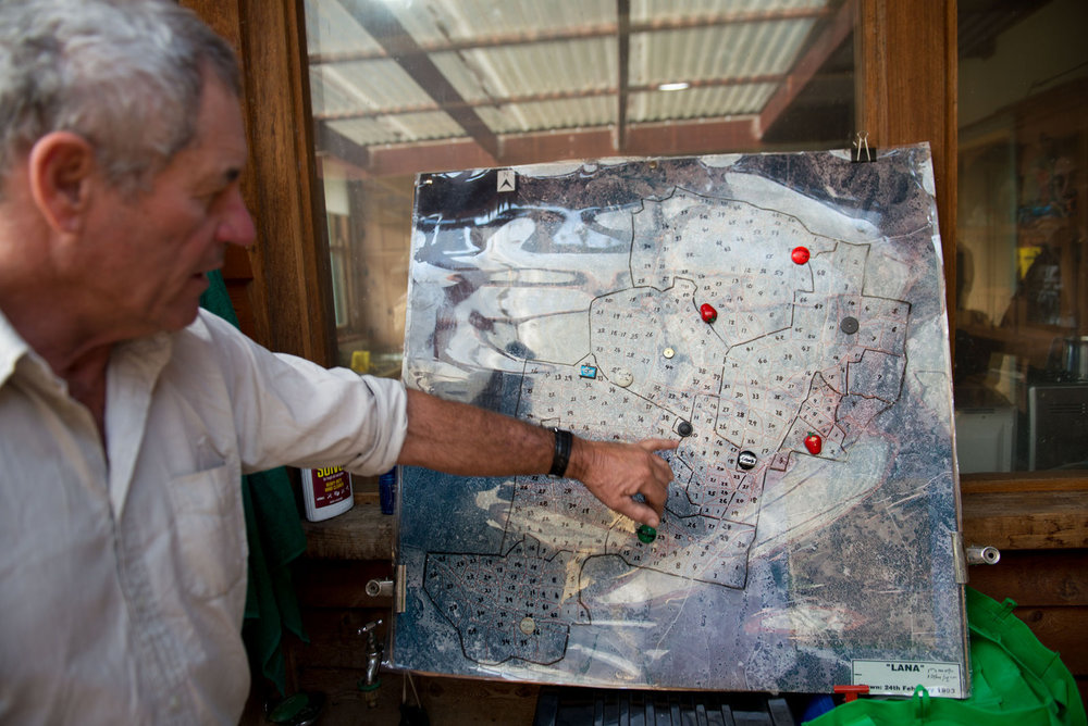 Tim with a map of his property that shows the small paddocks that his livestock move between following holistic management principles. Photo by Alex Wisser.