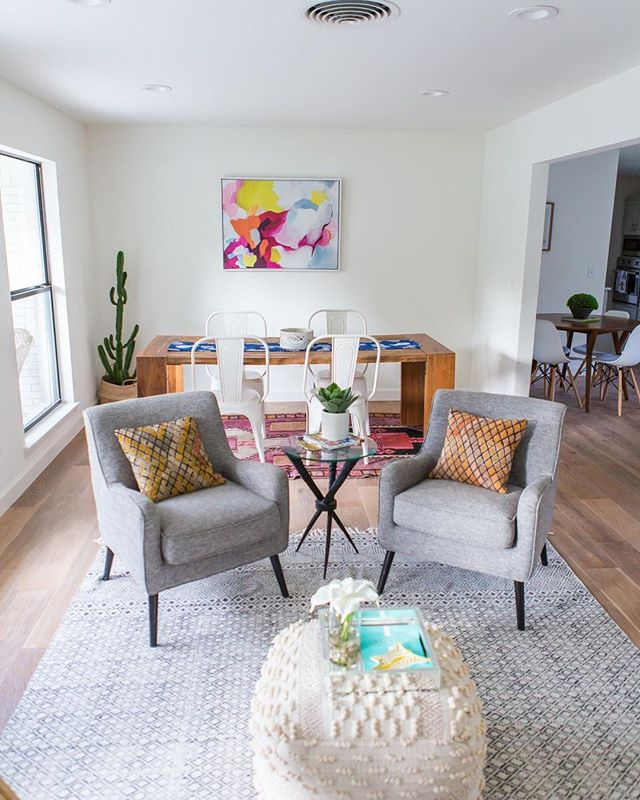 "Do you have a big, open room that you don't know what to do with? Perhaps it has many functions, but no clear division of space?⠀ ⠀ We took this extra-large front living room and divided it into  a sitting area and a formal dining area. How? RUGS! Rugs are always the answer! ⠀ ⠀ We have an 8x10 placed vertically to divide the sitting area and anchored it with a pair of chairs to create a conversation area - not pictured is another chair and a bar cart on the other wall 🍸Then we took a 5x7-ish rug placed horizontally under the table to create the ""dining area"". This creates clear division physically and, more importantly, visually to achieve a look that ""makes sense"" to your brain.⠀ ⠀ BIRDHOME Design ✨ #DesignForRealLife 📷: @homeglimpses"