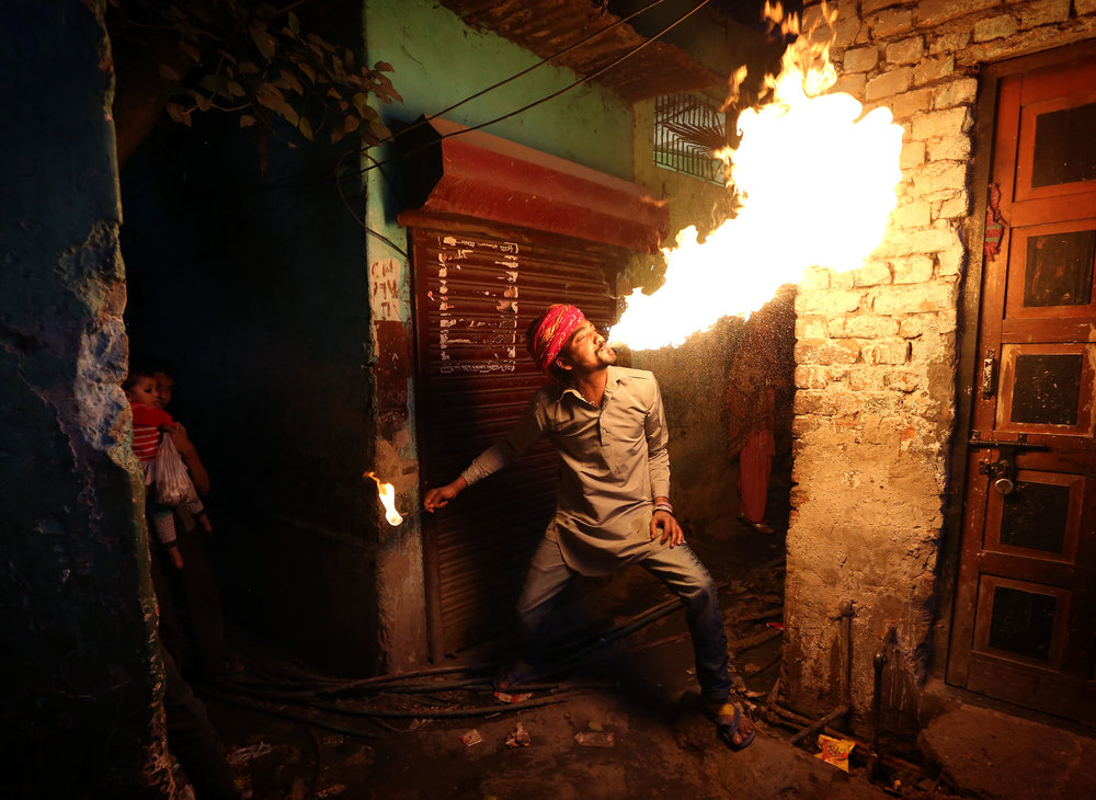 Fire breather Amit Kumar Bhatt practising his craft at his home in the Kathputli slum colony of New Delhi, India, December 10th, 2014. He is one of 40,000 people living in the slum, which is popularly known for being the worlds largest colony of street performers, including magicians, snake charmers, acrobats, singers, dancers, actors, traditional healers and musicians and puppeteers. Their livelihood is under threat however as the Delhi government has obtained contracts to demolish the colony to make way for developers to build high-rise apartments.