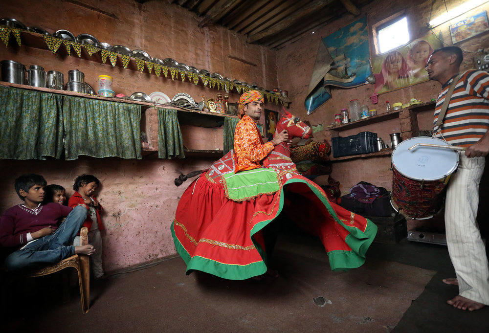 Jagdeesh Makkhan is pictured performing the Kachhi Ghodi traditional Rajasthani folk dance at his home in the Kathputli slum colony of New Delhi, India, December 7th, 2014. He is one of 40,000 people living in the slum, which is popularly known for being the worlds largest colony of street performers, including magicians, snake charmers, acrobats, singers, dancers, actors, traditional healers and musicians and puppeteers. Their livelihood is under threat however as the Delhi government has obtained contracts to demolish the colony to make way for developers to build high-rise apartments.