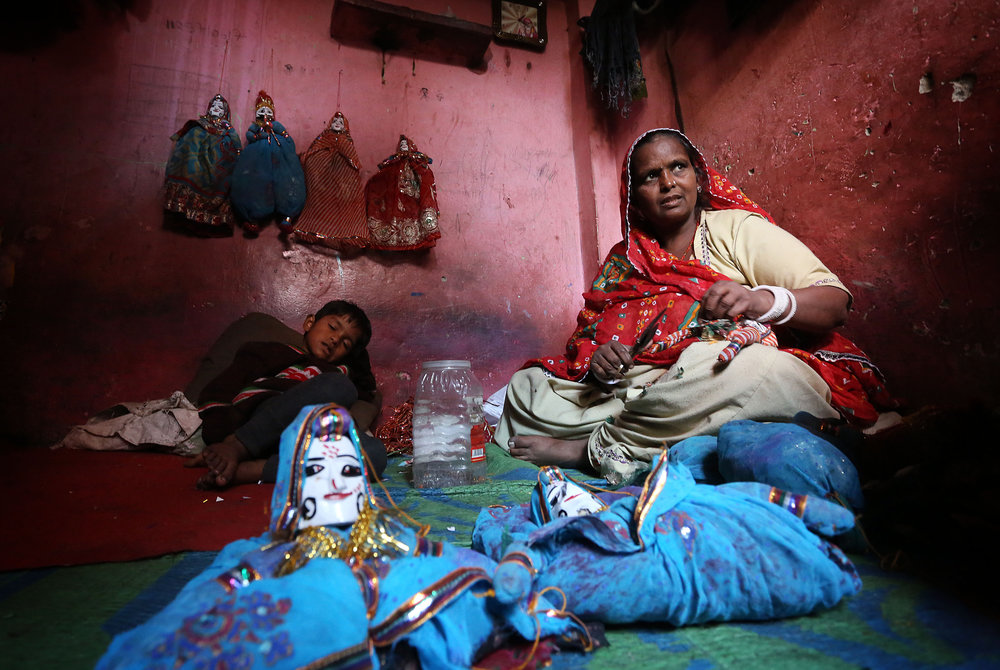 Rajasthani puppet maker Ghita Devi makes puppets alongside her son at her home in the Kathputli slum colony of New Delhi, India, December 8th, 2014. She is one of 40,000 people, speaking 11 different languages, living in the slum, which is popularly known for being the worlds largest colony of street performers, including magicians, snake charmers, acrobats, singers, dancers, actors, traditional healers and musicians and puppeteers. Their livelihood is under threat however as the Delhi government has obtained contracts to demolish the colony to make way for developers to build high-rise apartments.