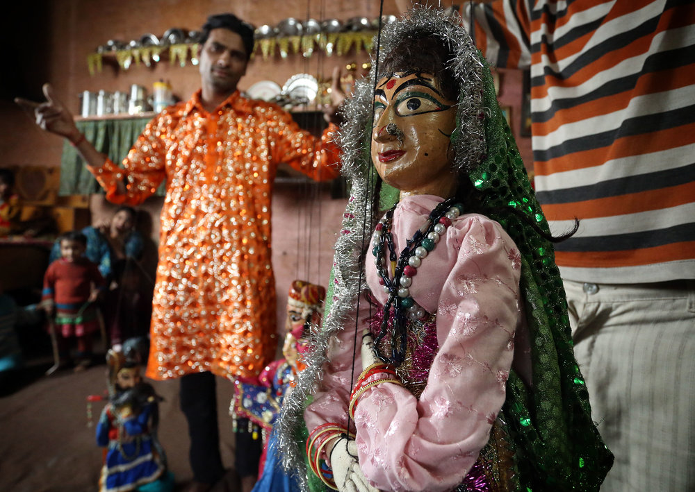 Jagdeesh Makkhan is pictured performing with Rajasthani puppets at his home in the Kathputli slum colony of New Delhi, India, December 7th, 2014. He is one of 40,000 people living in the slum, which is popularly known for being the worlds largest colony of street performers, including magicians, snake charmers, acrobats, singers, dancers, actors, traditional healers and musicians and puppeteers. Their livelihood is under threat however as the Delhi government has obtained contracts to demolish the colony to make way for developers to build high-rise apartments.