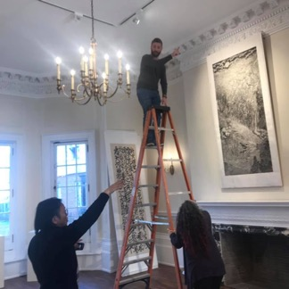 Sean on ladder on his first day, with Assistant Director of the IAC, Linda Weingarten, looking on, as Chinese Artist, Yu Hanyu, directs.