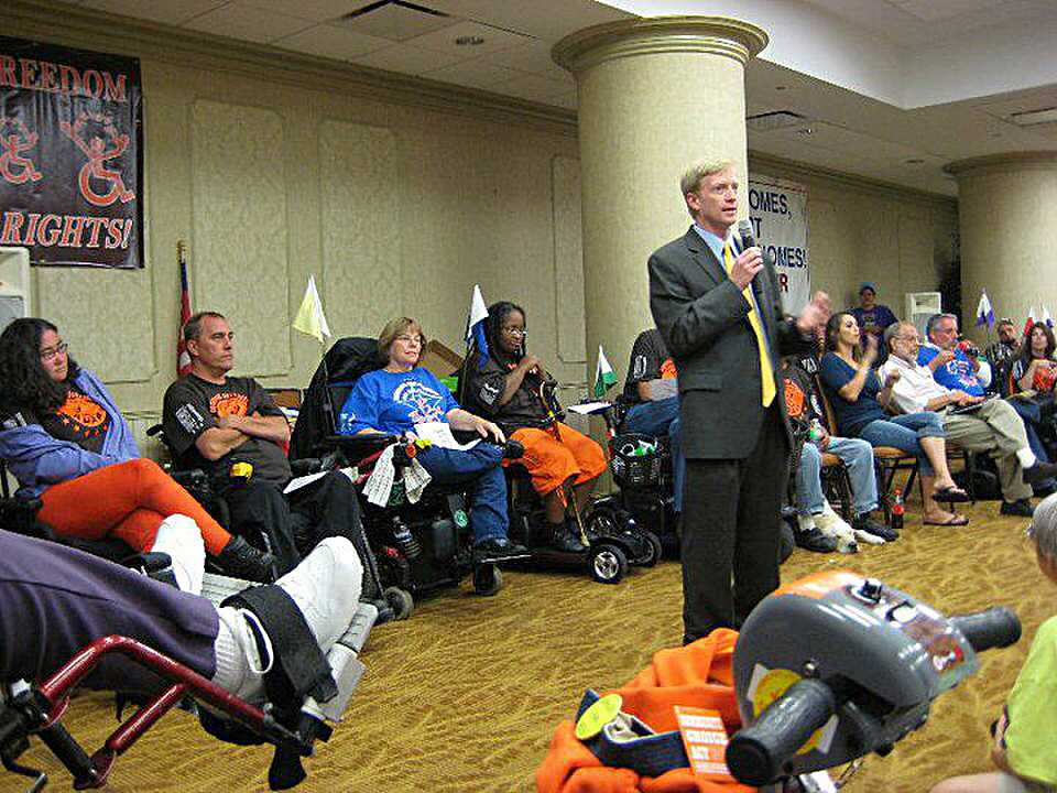 Sam speaks to the disability rights group ADAPT.