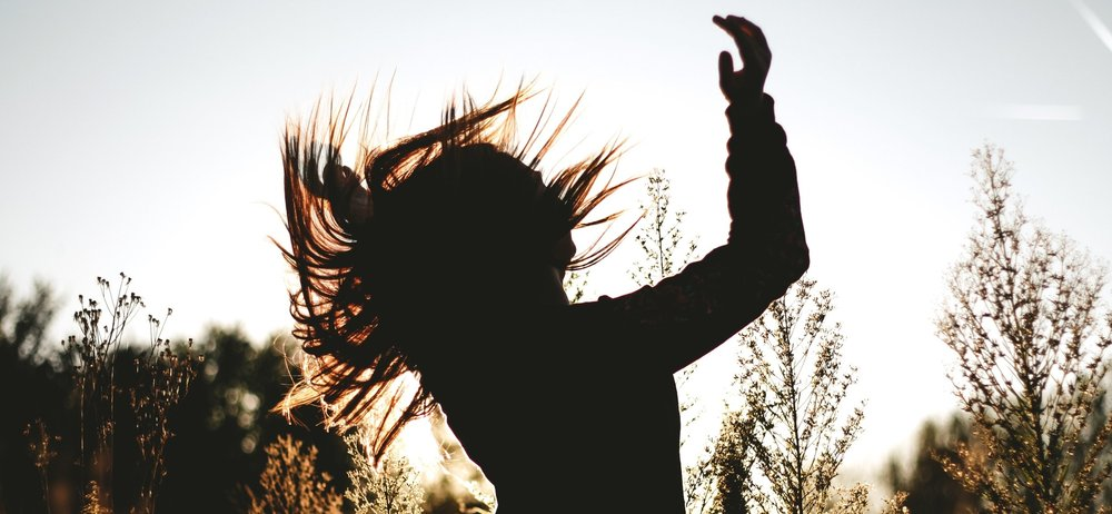 A girl in a meadow flipping her hair back. She is silhouetted by the sun behind her. You too can feel this good about your hair!