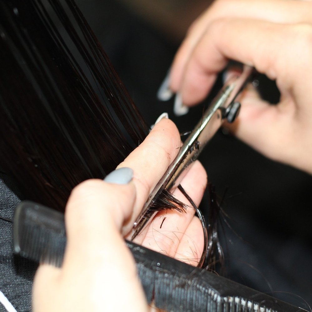 Closeup of hands cutting hair. Only a trained wig stylist should cut your synthetic wig.