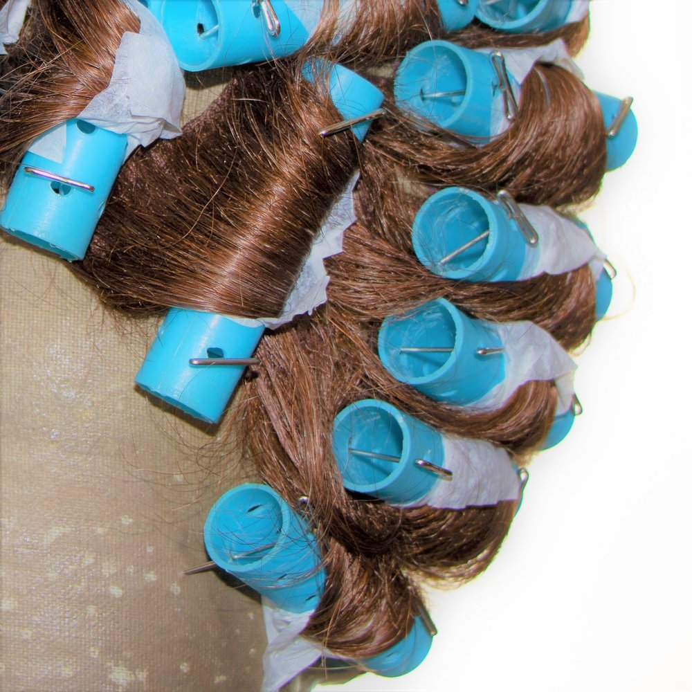 A closeup of a woman with curlers on her head. Setting and curling a wig requires specialized training and should only be undertaken by a trained wig stylist.