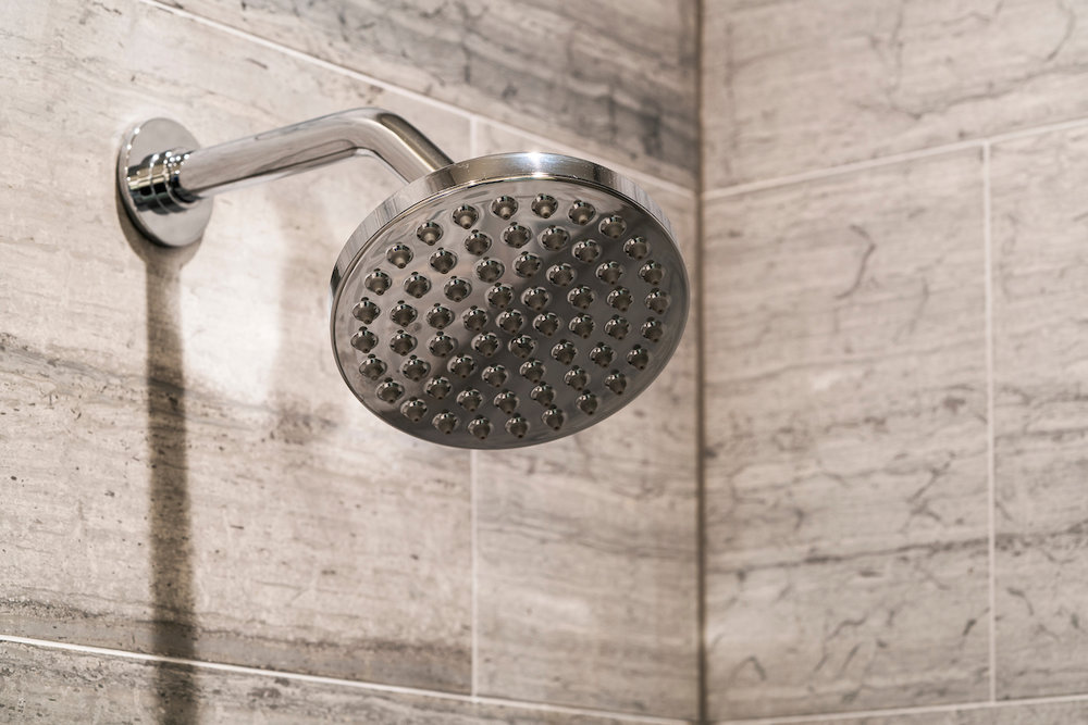 Waterworks rain shower heads and natural stone Waterworks tiling in the bathrooms.