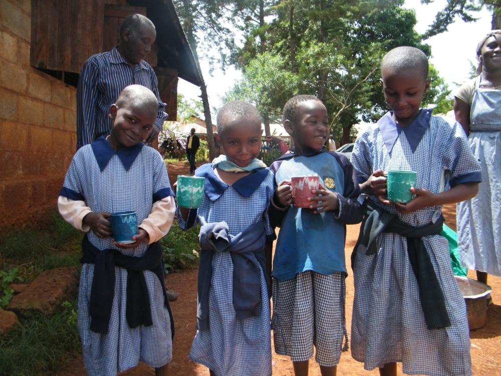 Four young Kenyan girls in blue school uniforms, holding mugs of porridge.