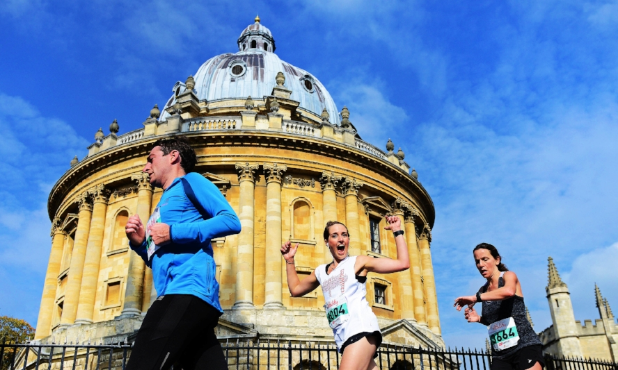A happy African Children's Fund half marathon runner, passing the Radcliffe Camera in Oxford in sunshine.