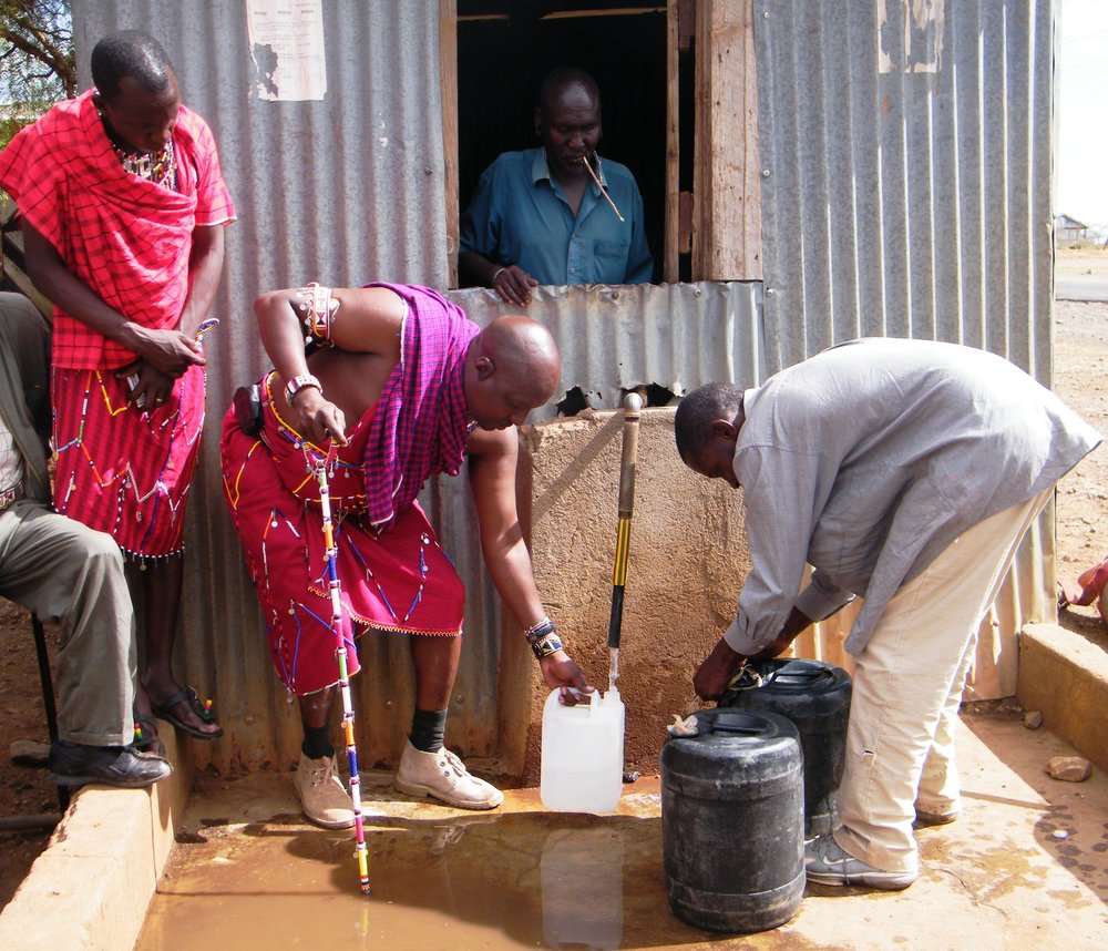 3 Kenyan men - two in traditional Maasai clothing - collecting water in different sized vessels from a stand pipe.