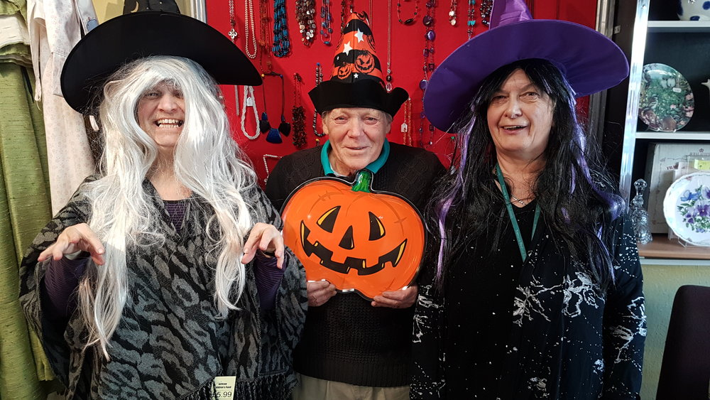 Three of our Witney volunteers posing in Halloween costumes in our charity shop.