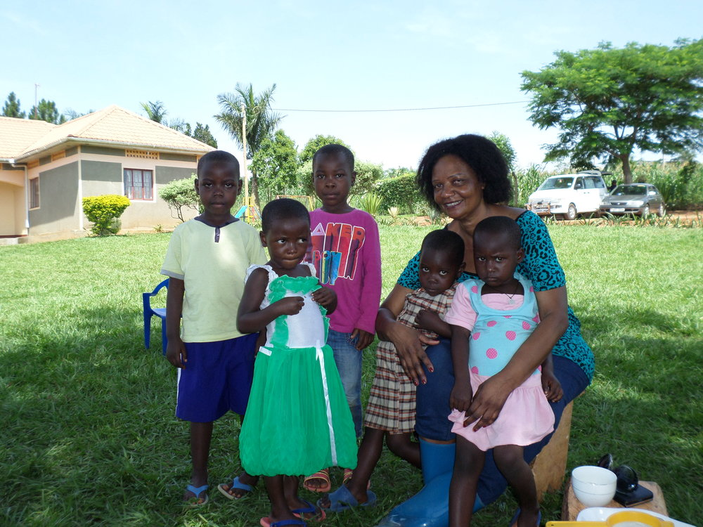 Social worker Judith with 5 children, on grass, in the shade outside the Nsimbe Transit Home.