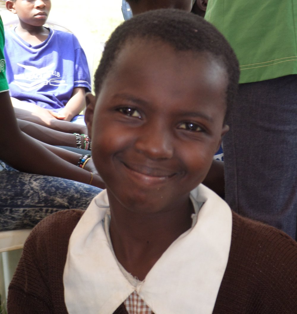 A girl wearing a brown jumper over white collars of her brown & white checked school dress, smiling