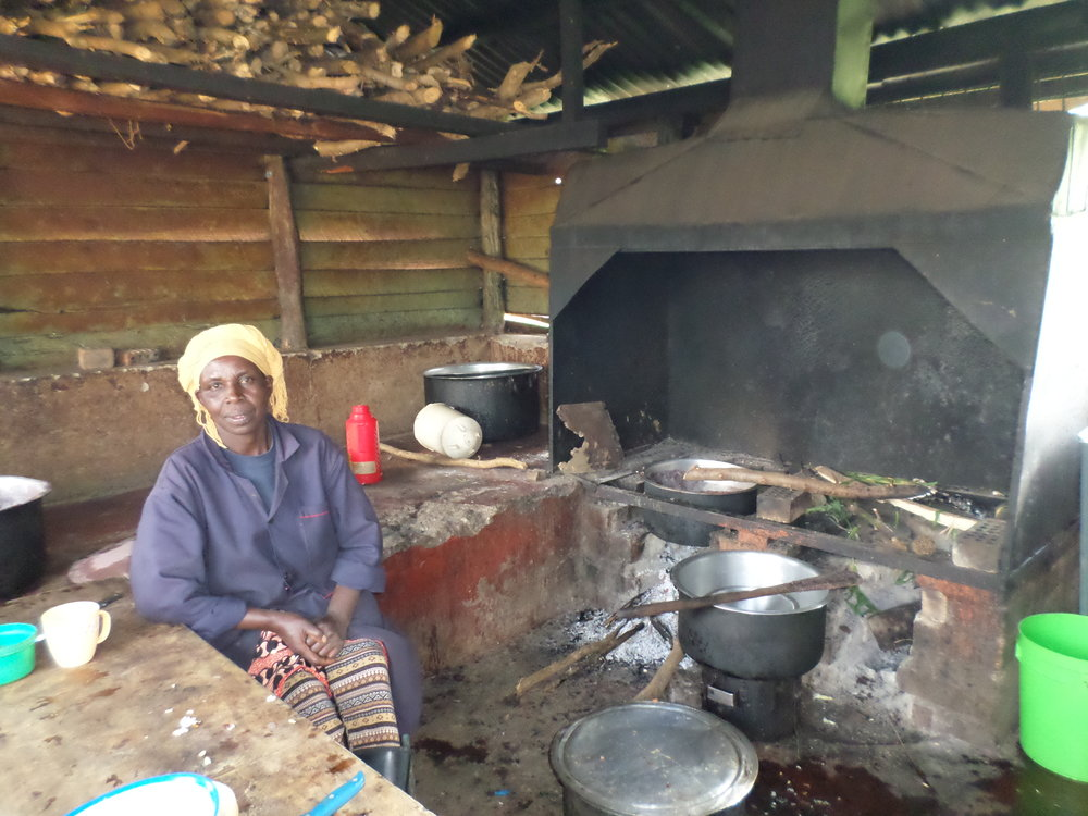 The school cook in a run-down kitchen, sitting with her back to ash from an open fire that has cooking pots on top and in front of it.