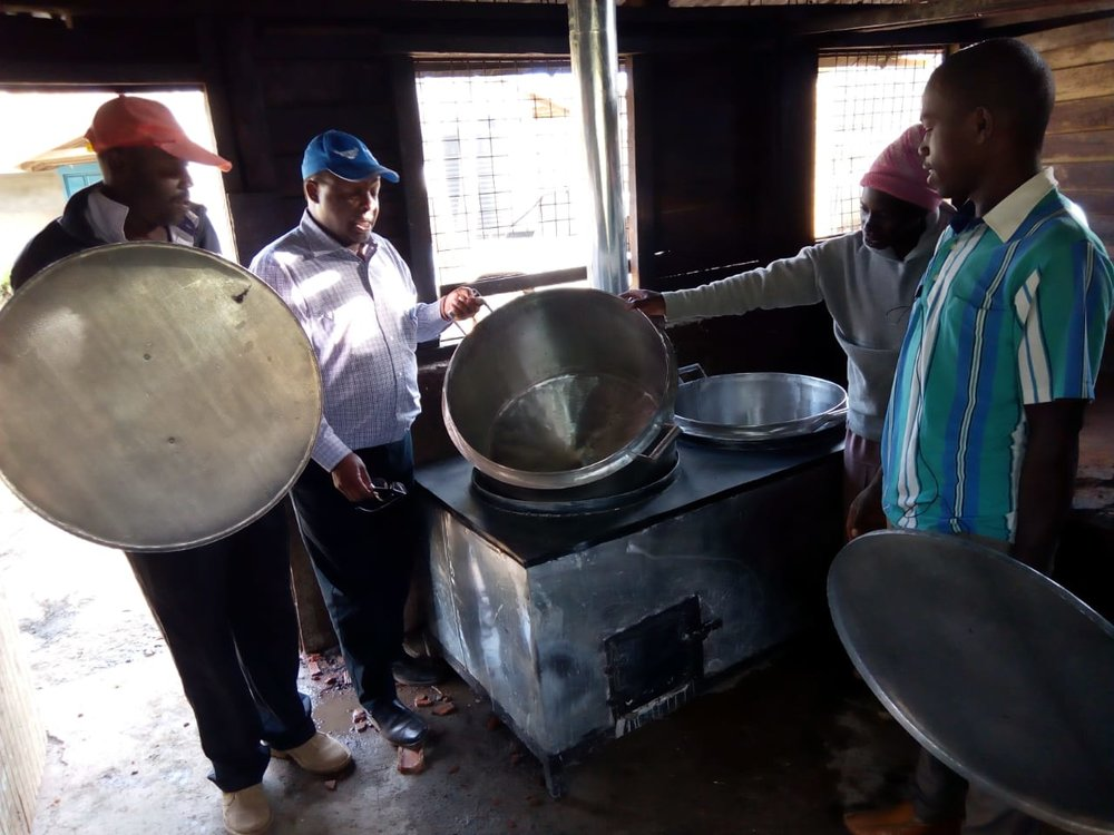 4 people in front of the new cooker, inspecting shiny, silver cooking pots