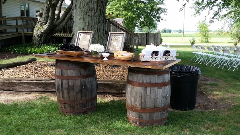 Wine Barrel Table - Description ~ wine barrels alone ca serve as cocktail tables or cake stands. Add your choice of tops to create a larger table.Quantity ~ 6 barrels, 2 topsRental Price ~ barrels $20, tops $25