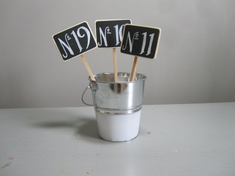 Chalkboard Table # - Description ~small chalkboard numbers on a stick that can be held in a bottle or centerpiece flowers to help your guests find their tableQuantity ~ 30Price ~ .50