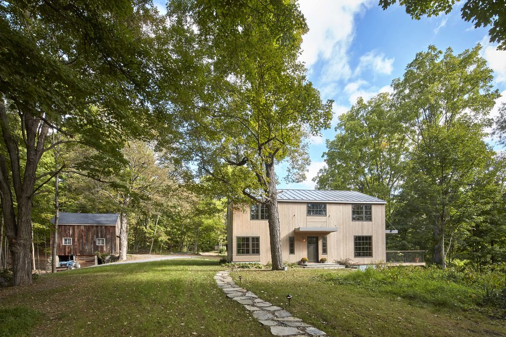 Fallkill Farm -  Year:  2016Type:  ResidentialLocation:  Hyde Park, NYSquare Footage:  2,350Scope of Work:  Architectural and Interior DesignAwards:  New York Cottages and Gardens 2017 Innovation in Design Award Winner, Architecture CategoryAn existing 1830's farmhouse located in historic Hyde Park, NY underwent a full-gut renovation to transform into a Rustic Modern retreat. A speculative project in collaboration with custom-home builder, Wolcott Builders, the two-story house sits on 36 acres and is surrounded by three large barns and a pond.The main goal of the project was to retain the house's historical elements such as exposed timber members and a stone hearth, which was built by the original owner with help from his children. In order to do so, we added modern details and amenities, incorporated purposeful elements and provided outdoor views of the beautiful property while maintaining the farmhouse vernacular. The result is a historic yet modern home that complements the surrounding structures.