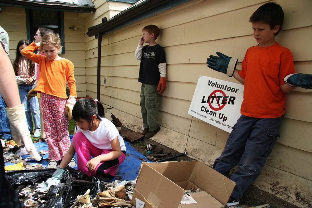 Students sorting trash and recyclables after participating in a Keep Rockland Beautiful community clean-up .