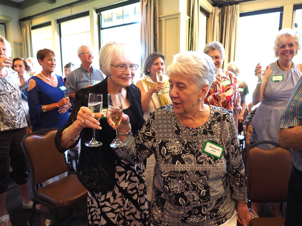 Nancy Popp and Margaret Smith are joined by other members in a toast.
