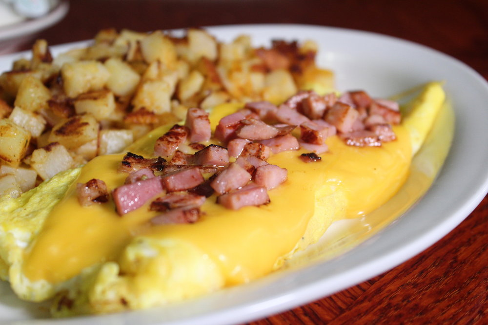 Ham egg and cheese omelet with golden hash browns.