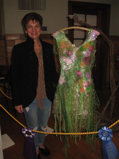 "Joann Ritter, winner of People's Choice in art, with painted plastic dress titled ""A Dress for the Fairy in My Garden."" It also won 1st place in the Mixed Media category."