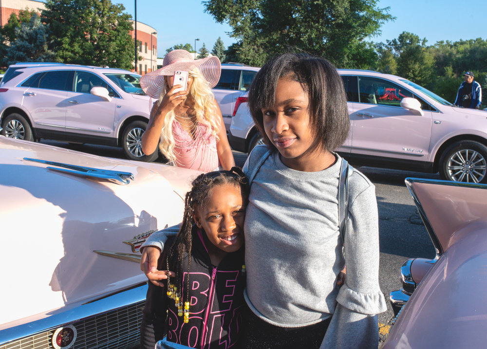 Mother With Her Two Daughters Posing With Pink Cadillacs