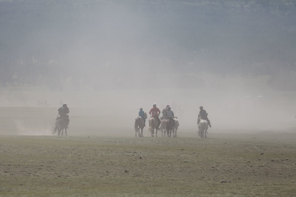 The riders, raising much dust, ride to the starting point of the races