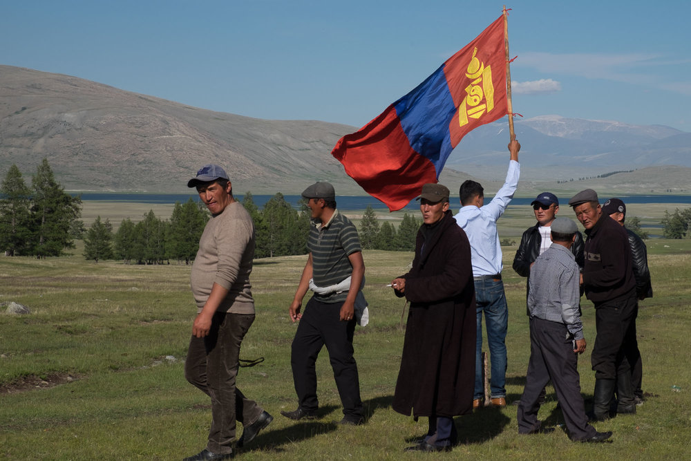 A race held as part of a wedding is sponsored by the groom, he holds the Mongolian flag at the finish line