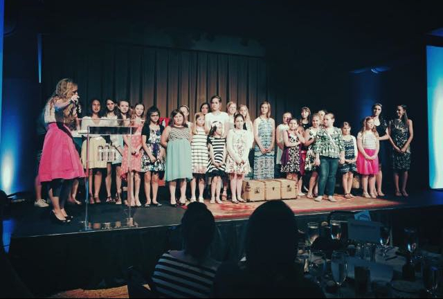 Heather standing with a group of girls that went through the Gracefully Strong program at their annual fundraise dinner.