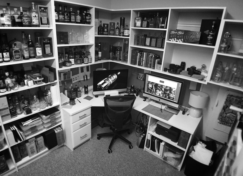 """This is David's desk. All the bottles you see here are purely related to work projects. When I asked about his """"whiskey collection,"""" he said it would be tough to capture. Like many of us, his personal collection is stashed around in various locations in his kitchen, basement and garage - and much of it is in cardboard boxes for long term storage."""