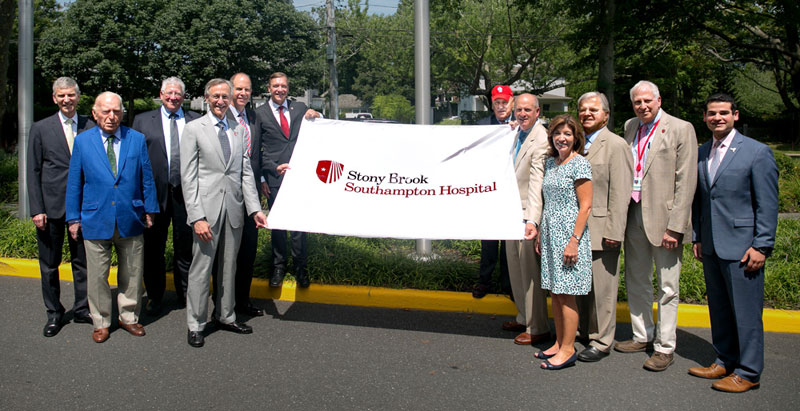 Raising the new Stony Brook Southampton Hospital flag at the celebration to introduce Stony Brook Southampton Hospital, from left, Cary F. Staller, Esq., SUNY Board of Trustees and Stony Brook Foundation Board of Trustees; Ambassador Carl Spielvogel, SUNY Board of Trustees; L. Reuven Pasternak, MD, Chief Executive Officer, Stony Brook University Hospital, and Vice President for Health Systems, Stony Brook Medicine; Kenneth Kaushansky, MD, Senior Vice President, Health Sciences, and Dean, Stony Brook University School of Medicine; Robert S. Chaloner, Chief Administrative Officer, Stony Brook Southampton Hospital; Samuel L. Stanley Jr., MD, President, Stony Brook University; Kenneth P. LaValle (R-Port Jefferson), New York State Senator; Kenneth B. Wright, Chair, Southampton Hospital Association Board; Kathy Hochul, New York State Lieutenant Governor; Fred W. Thiele Jr. (I-Southampton), New York State Assemblyman; Fred Weinbaum, MD, Chief Medical Officer and Chief Operating Officer, Stony Brook Southampton Hospital; and Marc Cohen, SUNY Board of Trustees.