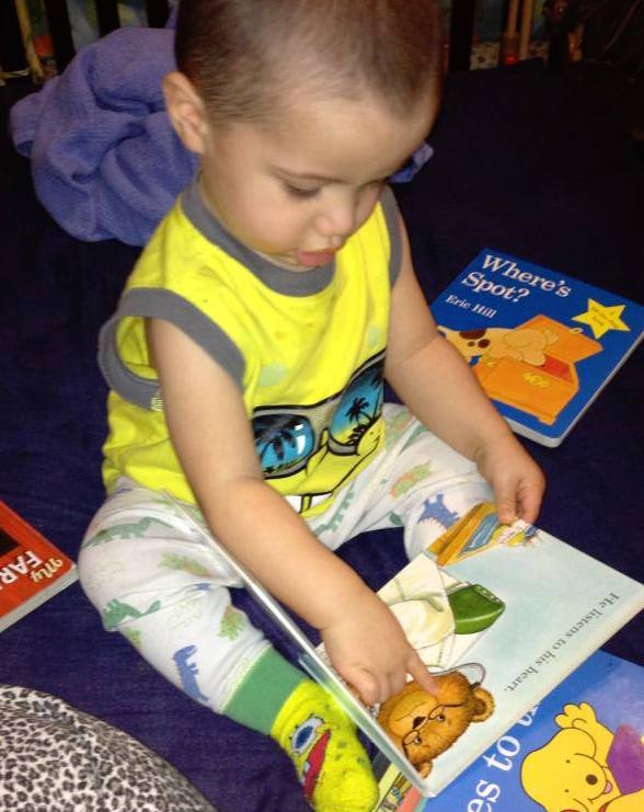 brown toddler boy touching picture books scattered crop.jpg