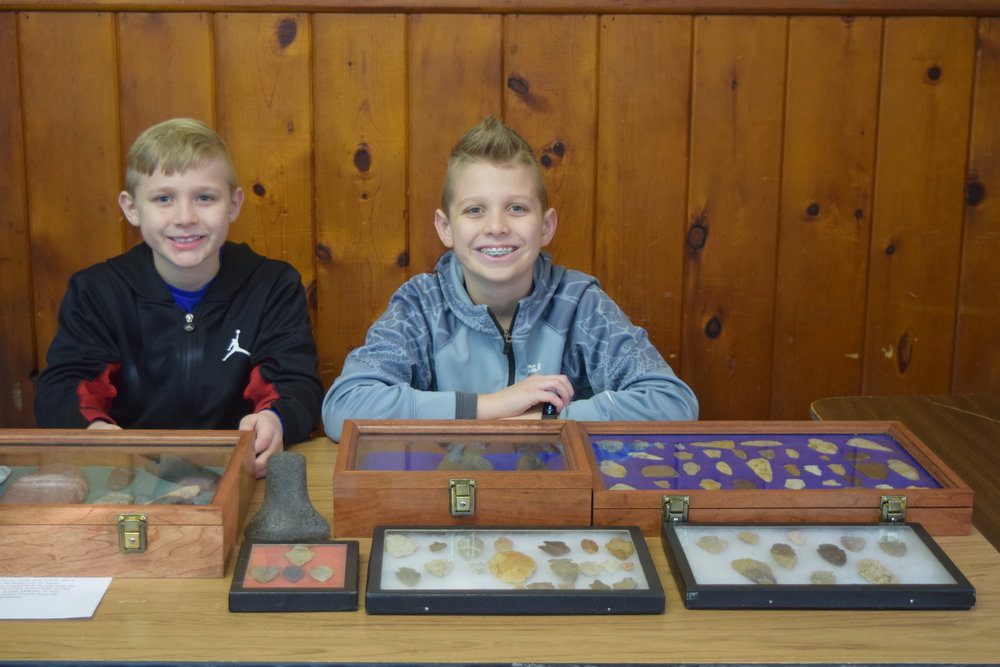 Bennett and Graham Kill with their display. Not pictured is Reid Kill. All three of these young archaeologists won prizes for their 2017 finds.