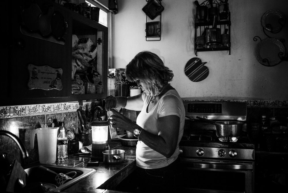 Photo credit: Aniya Emtage Legnaro  Yolanda Perez makes a coffee by lamp as she recounts the morning of the hurricane. She tells us that her son died a few months before the hurricane, and she had not been in his room since his death. The hurricane forced her and eight others into his room because it was the only safe place.