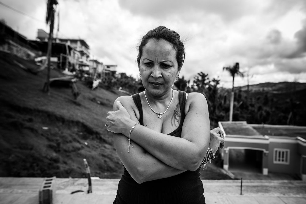 Photo credit: Aniya Emtage Legnaro  Juan's wife Denisse, listens as her husband speaks of his hopes of rebuilding the home for his family. Orocovis, Puerto Rico