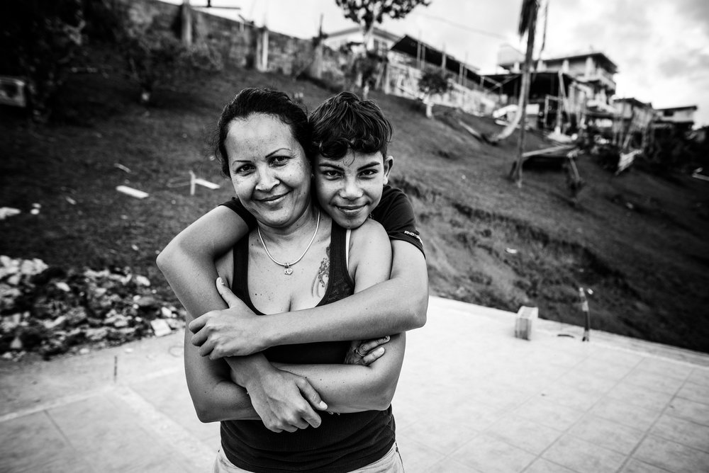 Photo credit: Aniya Emtage Legnaro  Denisse and her son, Xabdiel, 13, photographed on the remaining floor structure of their destroyed home. Orocovis, Puerto Rico