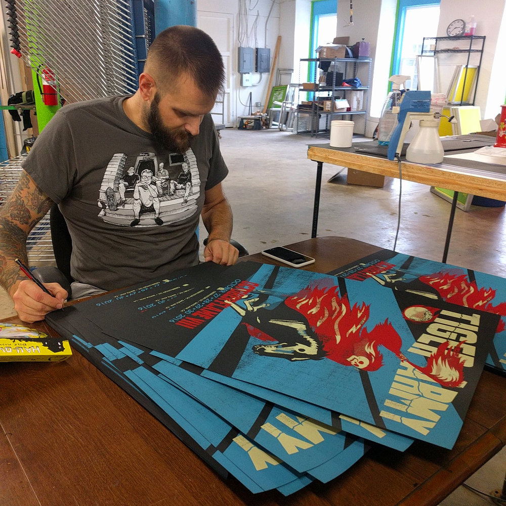 Artist Linas Garsys signing the prints he      designed for the band Tiger Army
