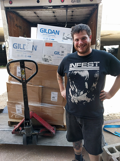 President of Sage Screenprinting, Dan, unloading a truck loaded with shirts.