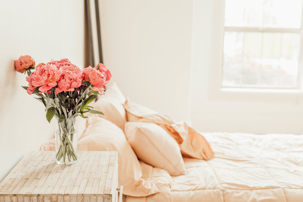 Pink peonies bring a spark of joy to a minimalist bedroom.