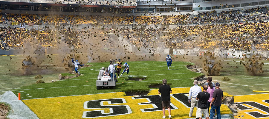A photo taken on the day I visited the set of  The Dark Knight Rises , featuring Hines Ward running towards the camera as charges filled with debris go off all over Heinz Field in Pittsburgh.