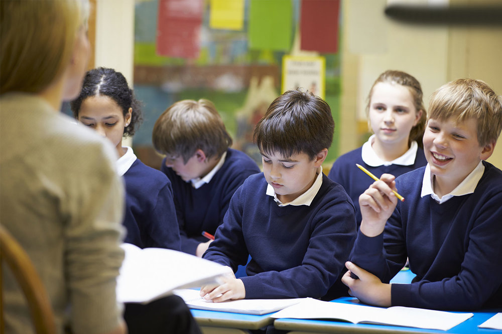 Teacher-Teaching-Lesson-To-Elementary-School-Pupils.jpg